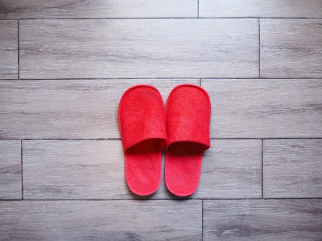 木製の床タイルに赤い家の布使い捨てスリッパ