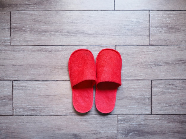 Red home fabric disposable slippers on wooden floor tile