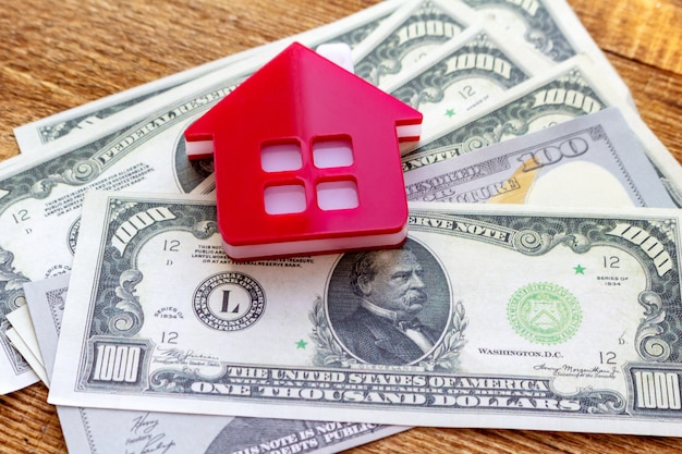 Red home house on the banknotes background euro dollar pile pack real estate concept expenses property buying copy space close up background selective focus