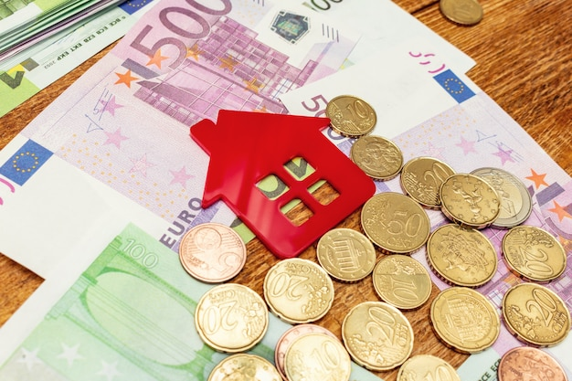 Red home house on the banknotes background euro dollar pile pack real estate concept