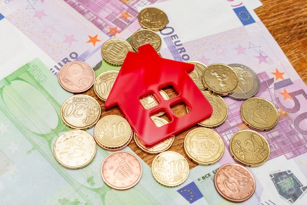 Red home house on the banknotes euro dollar pile pack real estate concept expenses property buying