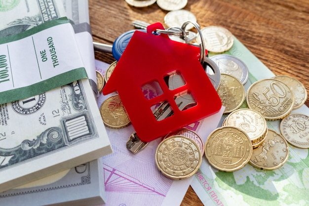 Red home house keys on the banknotes and coins background euro pile pack real estate concept expenses