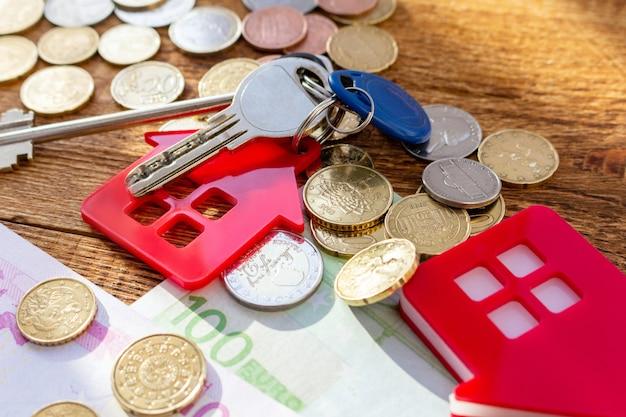 Красные домашние ключи от дома на фоне банкнот и монет. покупка недвижимости, концепция расходов на недвижимость.