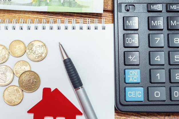 Red home house notepad pen on the banknotes and coins
