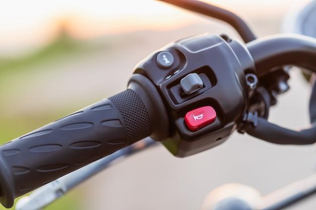 赤いホーンスイッチ。オートバイのハンドクラッチ付きマクロ左ハンドルバー。日没効果のあるオートバイのメンテナンスコンセプト屋外撮影