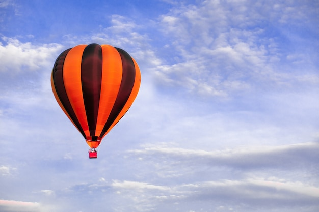 Red hot air balloon flying on blue sky, delivery concept