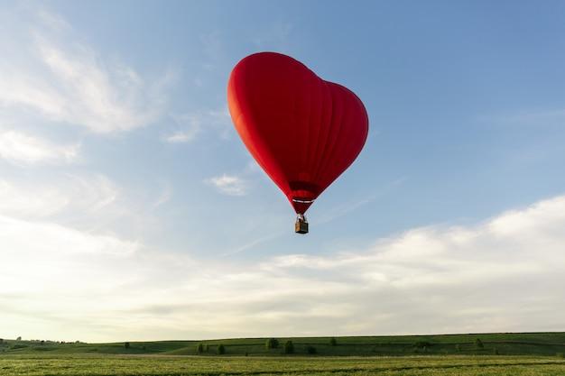 Красный воздушный шар в форме сердца летать в небе. любовь, медовый месяц и романтическая концепция путешествия