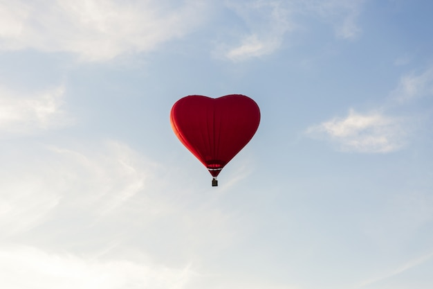 Red hot air balloon in the shape of a heart fly in sky. love, honeymoon and romantic travel concept