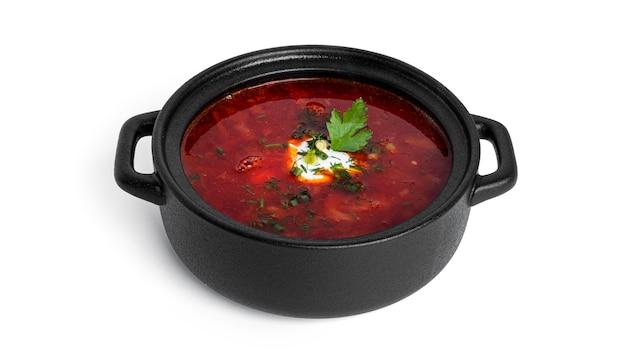 Красный, горячий борщ - свекольный суп со сметаной и зеленью в черном горшочке, изолированном на белом.