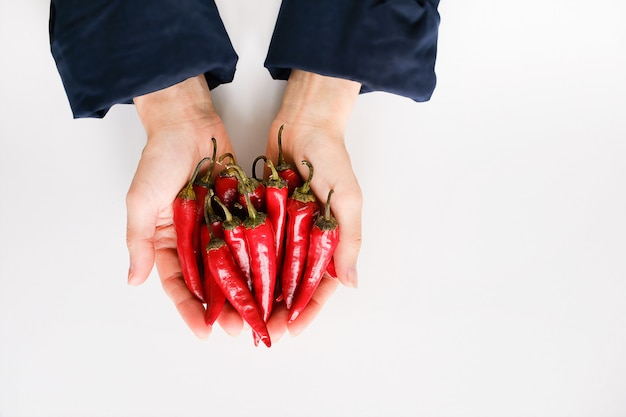 Red hot chili pepper in the hands of a woman on a white background