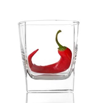 白で隔離のガラスの赤唐辛子