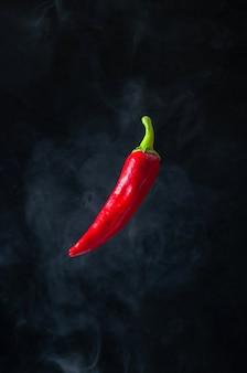 Левитация red hot chili pepper в воздухе с дымом на черном фоне.