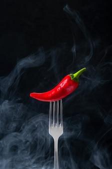 Красный острый перец чили на вилке с дымом на черном фоне.