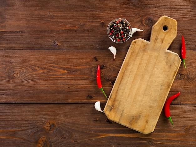 赤唐辛子のさやとエンドウ豆、まな板、ニンニクのクローブ