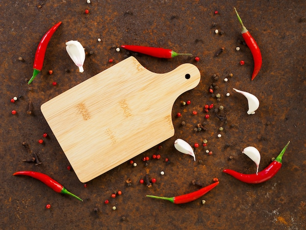 Red hot chili pepper pods and peas, cutting board, garlic clove on dark rusty metal background