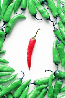 Red hot chili pepper on a white background, around a stack of green pods.