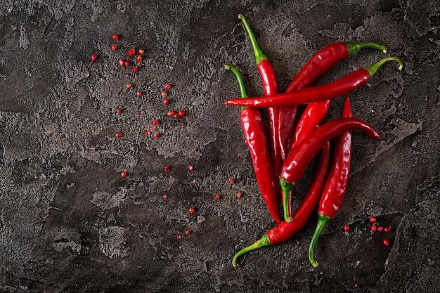 Краснокалильные перцы chili на серой таблице.
