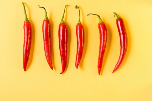 Red hot chili peppers pattern on yellow background,