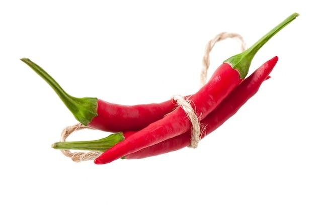 Красный острый перец чили перевязанный веревкой на белом