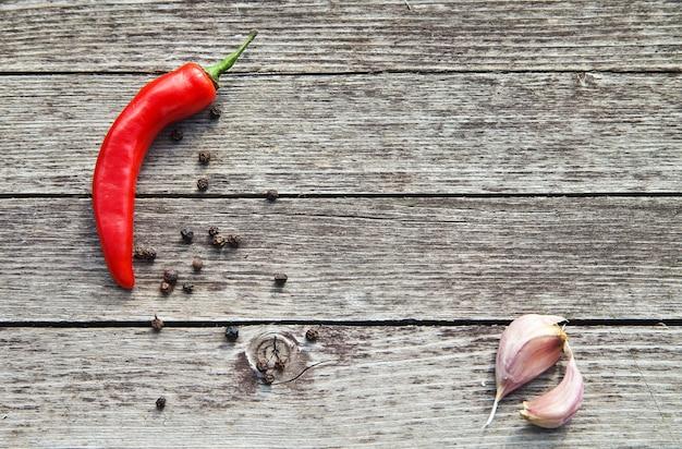 Красный острый перец чили с чесноком на деревянных фоне