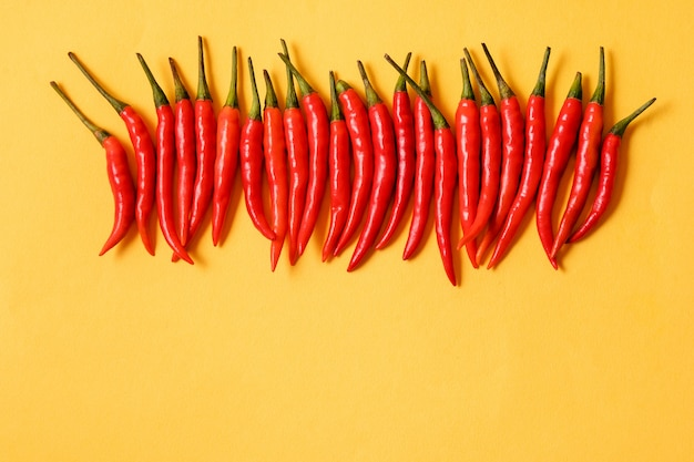Red hot chili peppers on yellow background,