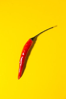 Red hot chili peppers on yellow surface.