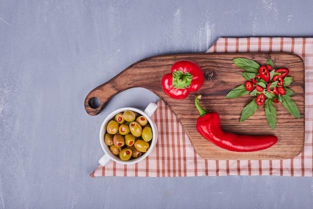 Красный острый перец чили с маринованными оливками на деревянной доске.