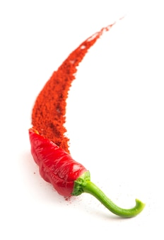 Red hot chilies with powder over white surface.