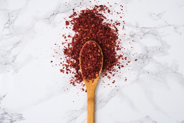 Red hot chilli pepper flakes in wooden spoon