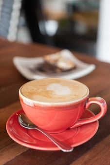 Red hot coffee cup and bakery on wood table in restaurant