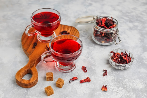 Red hot hibiscus tea in a glass mug on concrete  with dry hibiscus petals