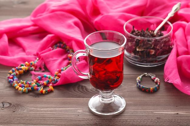 木製のテーブルと乾燥茶カスタードのガラスのマグでレッドホットハイビスカスティー
