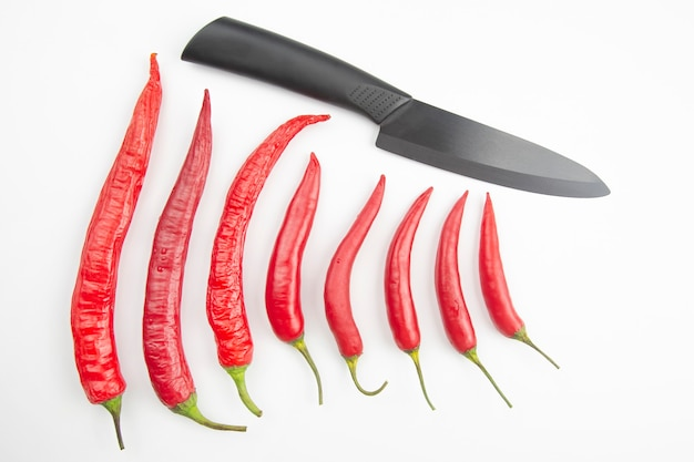 붉은 고추와 화이트 블랙 세라믹 부엌 칼. 건강한 식물성 식품 및 비타민