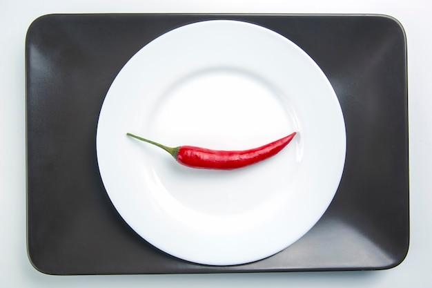 Красный острый перец на белой тарелке