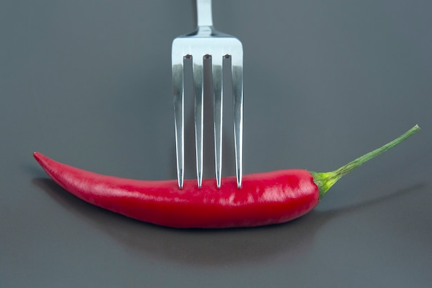 Red hot pepper with fork close-up on grey wall.