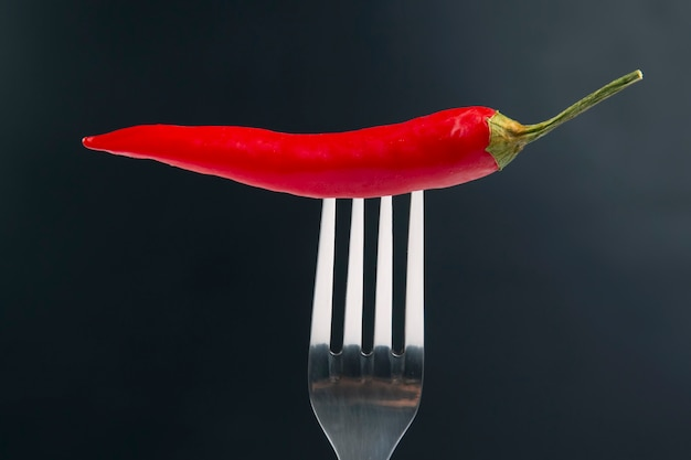 赤唐辛子とフォークのクローズアップ。健康的な野菜食品とビタミン
