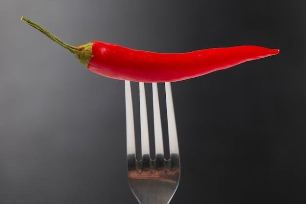 Красный острый перец с вилкой крупным планом на темноте