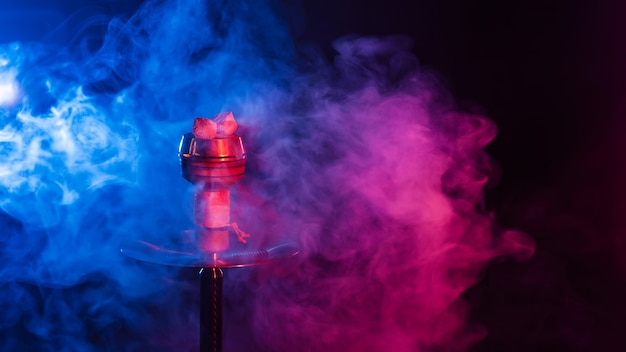 Red hot shisha coals in a metal hookah bowl against a background of multicolored smoke close up with a copy space
