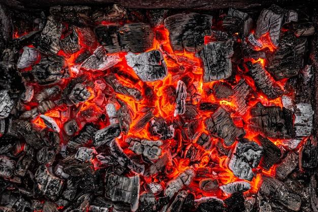 Раскаленный белый и черный уголь тлеет на барбекю перед жаркой мяса