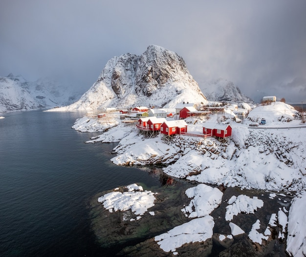 Red house fishing village with snow mountain in snowfall day