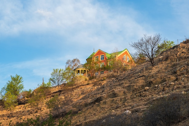 山の頂上にある赤い家。グニブ村のゲストハウス。コーカサス山脈の岩の上にある孤独な家。ダゲスタン。