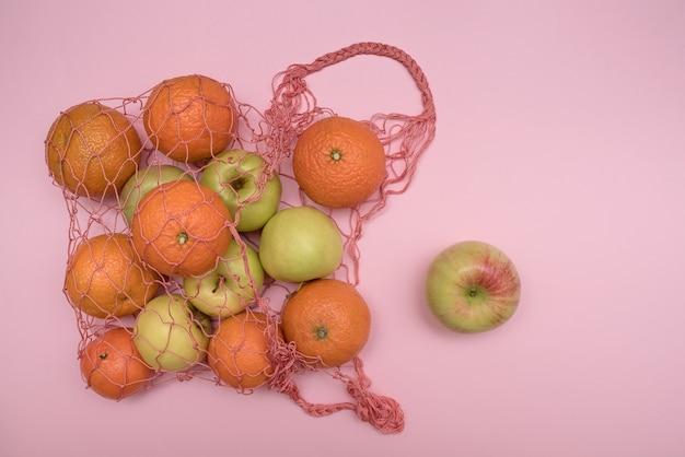 Красная бытовая сетка на розовой поверхности с фруктами. яблоки и мандарины. на десерт.