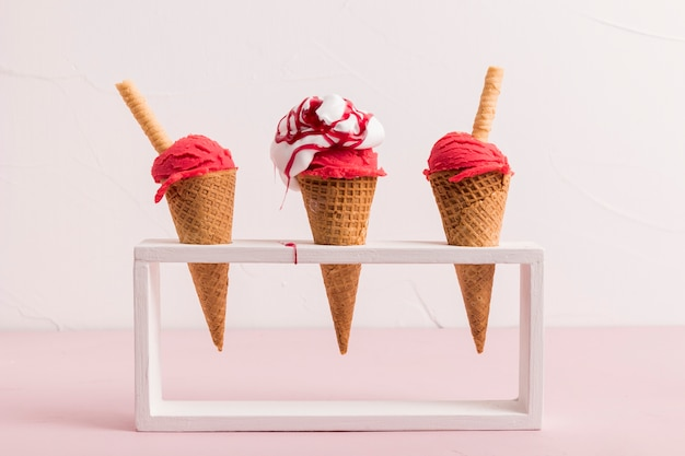 Red ice cream scoop in cones with syrup and waffle straw on stand