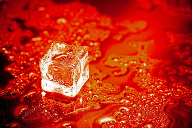 Red ice cubes reflection on black table background.