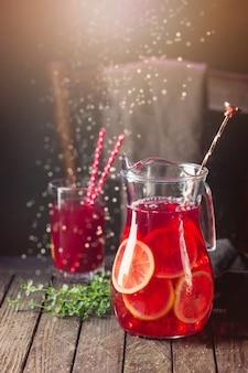 Красный ледяной лимонад с нарезанными свежими лимонами в кувшине на темном дереве
