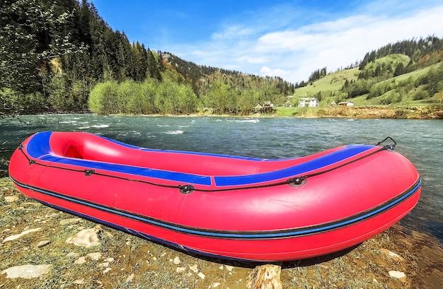山の川の岸でラフティングのための赤の膨脹可能なボート