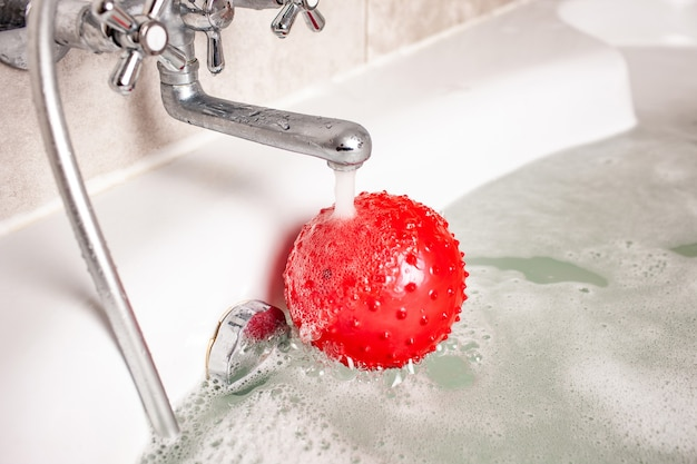 Red inflatable childrens ball lies under a stream of water in the foam bath