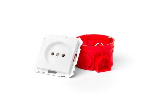 Красный монтажный электрический ящик для розеток и белых розеток и проводов на бетонном фоне.