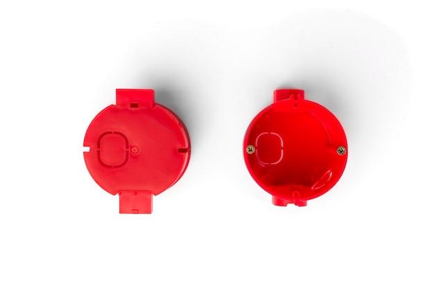 Красный монтажный электрический ящик для розеток и проводов на бетонном фоне.