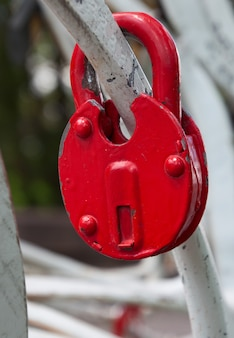 Red iron lock on a white fence